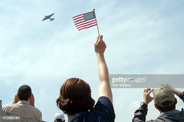 A spectator waves to World War II era aircraft as they fly over the World War II Memorial on the Mall to commemorate the 70th anniversary of the...