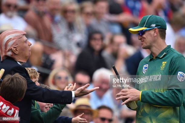 A spectator wearing a mask of US President Donald Trump tries to shake hands with South Africa's Chris Morris during the second OneDay International...