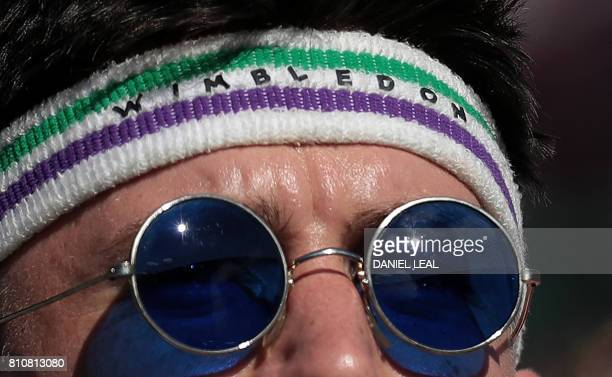 A spectator wears a headband that reads 'Wimbledon' as he watches a match at The All England Lawn Tennis Club in Wimbledon southwest London on July 8...