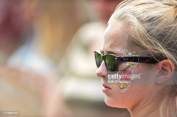 A spectator wears facepainting of a strawberry on her cheek on day three of the 2013 Wimbledon Championships tennis tournament at the All England...