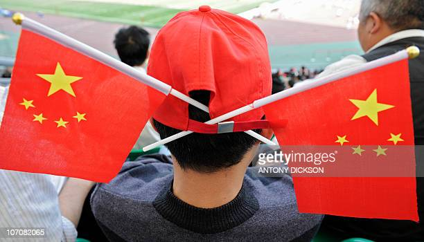 A spectator with Chinese flags fixed on his cap watches the men's rugby matches at the University town main stadium in Guangzhou during the 16th...