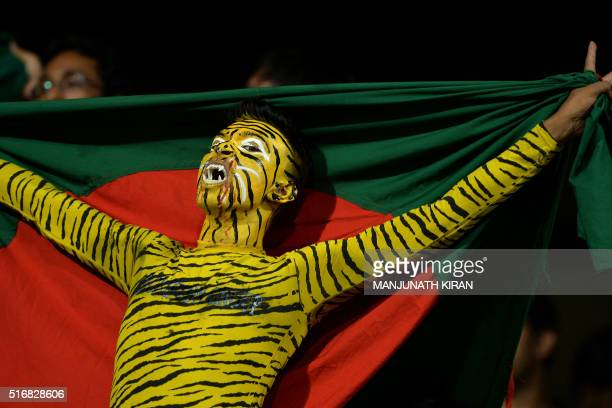 A spectator with his body painted holds a Bangladeshi flag as he cheers for his team during the World T20 cricket tournament match between Australia...
