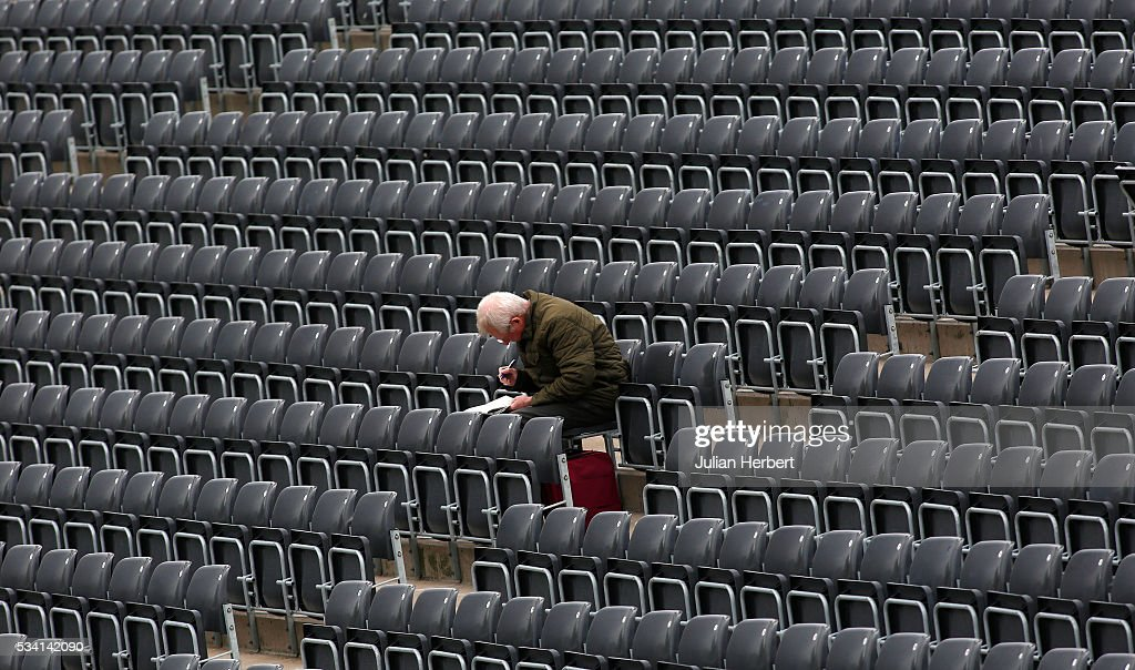 A spectator works on a newspaper crossword puzzle during day four of the Specsavers Division Two match between Gloucestershire and Northamptonshire at The County Ground on May 25, 2016 in Bristol, England.