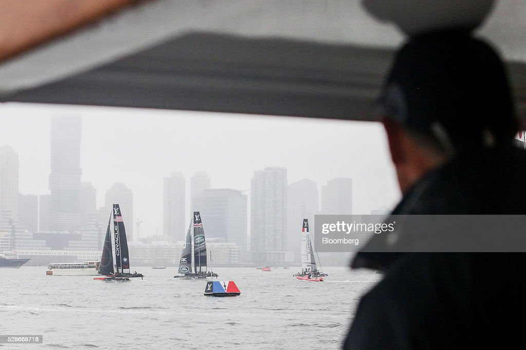 Spectators aboard the Land Rover hospitality boat watch as team catamarans sail during practice ahead of the Louis Vuitton America's Cup World Series races in New York, U.S., on Friday, May 6, 2016. The America's Cup sailing races are held in New York City on the Hudson River for the first time since 1920. Photographer: Chris Goodney/Bloomberg via Getty Images