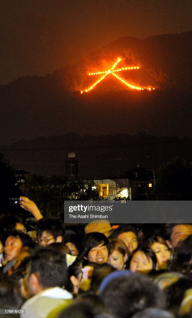 Spectators admire the Daimonji hillside bonfire as part of the annual Gozan Okuribi festival on August 16, 2013 in Kyoto, Japan.
