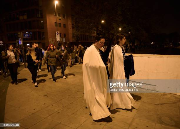 Spectators an penitents leave a Holy Week processional area following a stampede in Sevilla on April 14 2017 An outbreak of panic sparked by...
