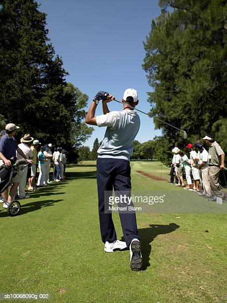 Spectators and male golfer on course