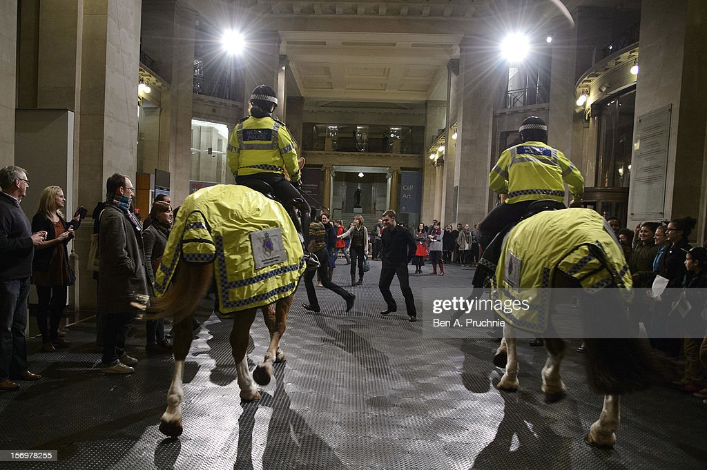 Spectators and mounted police officers take part in shortlisted artist Tania Bruguera's performance Tatlin's Whisper #5 at the National Museum Wales as part of the Artes Mundi 5 exhibition and prize to be awarded on Thursday 29th November at National Museum Cardiff on November 26, 2012 in Cardiff, Wales.