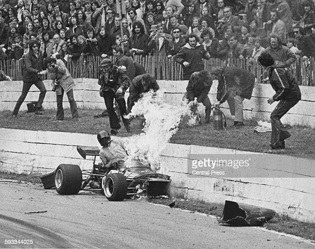 Spectators and photographers look on as track marshals prepare their fire extinguishers as Dick Barker driving the Richard Barker Racing Brabham BT28...