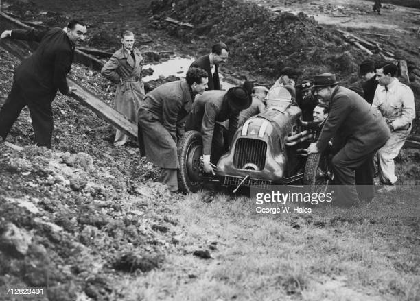 Spectators and track marshals come to the assistance of John Appleton after crashing his AppletonRiley Special during practice for the Coronation...