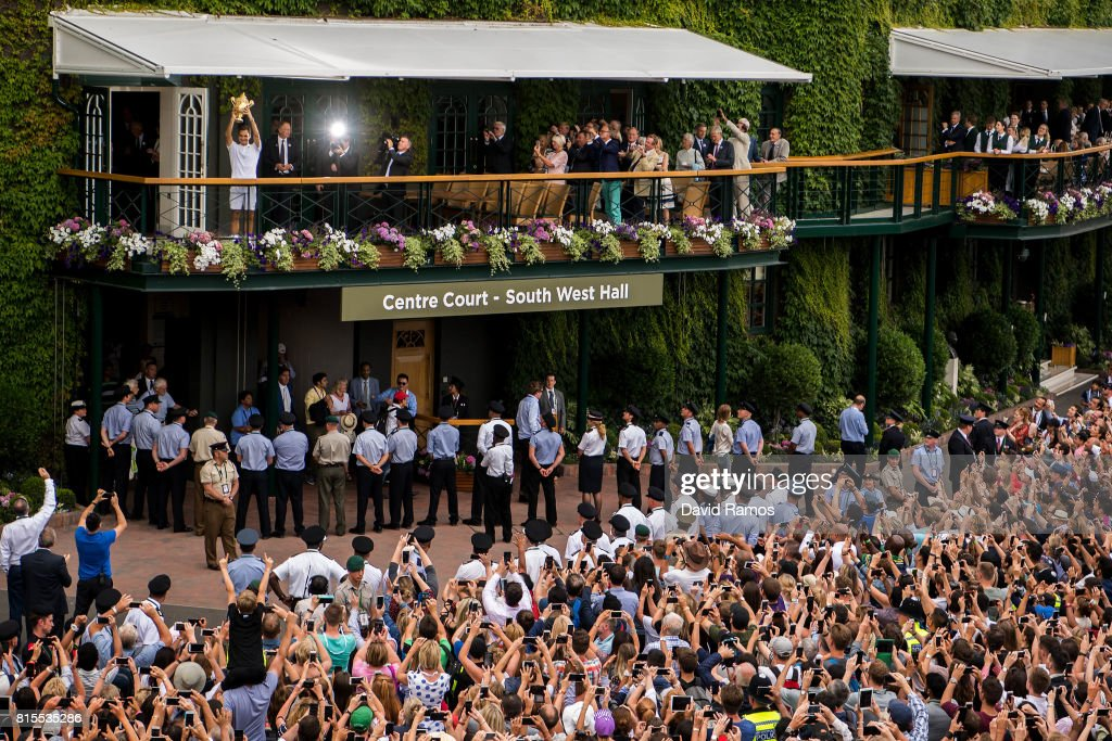 Spectators applaud and take photographs as Roger Federer of Switzerland celebrates victory with the trophy on the balcony after the Gentlemen's Singles final against Marin Cilic of Croatia on day thirteen of the Wimbledon Lawn Tennis Championships at the All England Lawn Tennis and Croquet Club on July 16, 2017 in London, England.