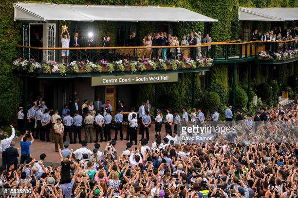 Spectators applaud and take photographs as Roger Federer of Switzerland celebrates victory with the trophy on the balcony after the Gentlemen's...