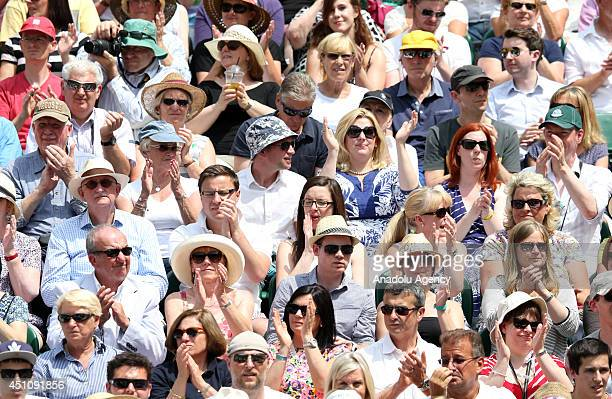 Spectators applaud Andy Murray as he arrives the Centre Court with Belgium's David Goffin for their men's singles first round match during the 2014...