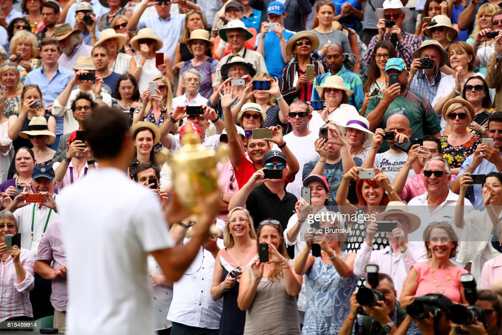 Spectators applaud as Roger Federer of Switzerland celebrates victory with the trophy after the Gentlemen's Singles final against Marin Cilic of Croatia on day thirteen of the Wimbledon Lawn Tennis Championships at the All England Lawn Tennis and Croquet Club at Wimbledon on July 16, 2017 in London, England.