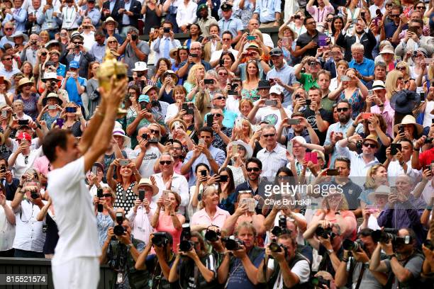 Spectators applaud as Roger Federer of Switzerland celebrates victory with the trophy after the Gentlemen's Singles final against Marin Cilic of...