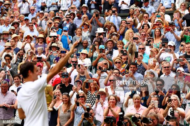 Spectators applaud as Roger Federer of Switzerland celebrates victory after the Gentlemen's Singles final against Marin Cilic of Croatia on day...