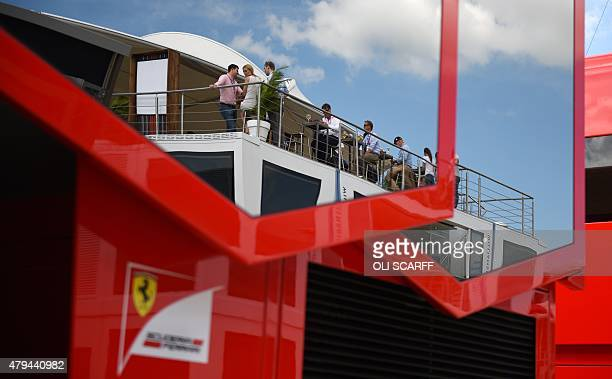 Spectators are reflected in the windows of the Ferrari team base in the paddock after the qualifying session at the Silverstone circuit in...