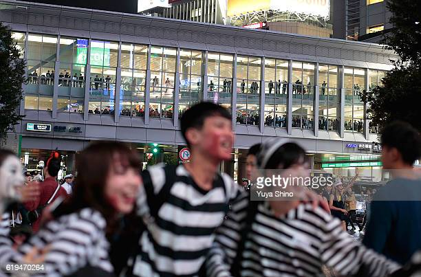 Spectators are seen inside a overpass of Shibuya train station during Halloween celebrations at Shibuya district on October 31 2016 in Tokyo Japan
