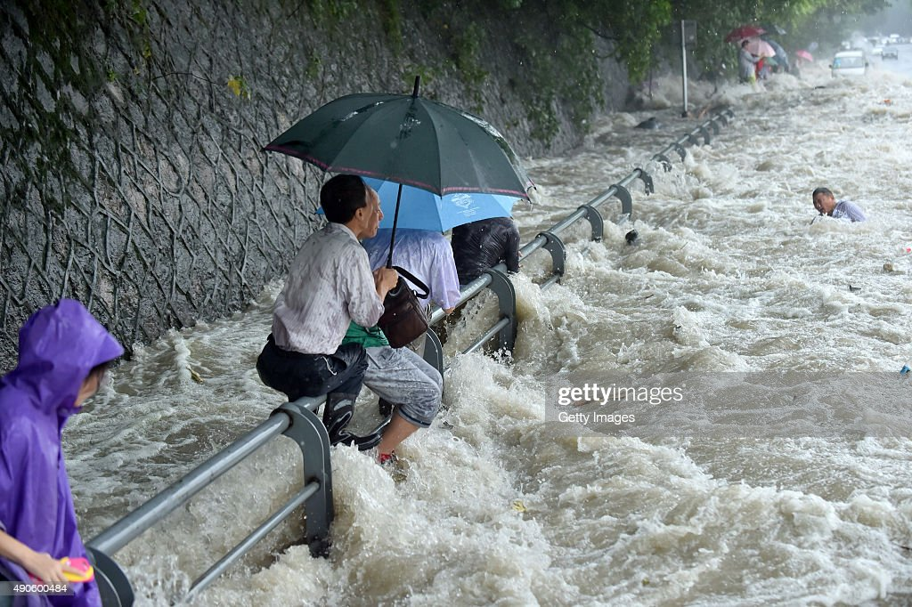 Spectators are swept by huge waves brought by Typhoon Dujuan while watching tides of Qiantang River at a dike on September 29 2015 in Hangzhou China...