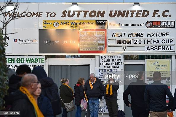 Spectators arrive at the stadium ahead of the English FA Cup fifth round football match between Sutton United and Arsenal at the Borough Sports...