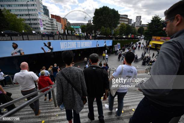 Spectators arrive at Wembley Stadium in London on August 20 2017 for the English Premier League football match between Tottenham Hotspur and Chelsea...