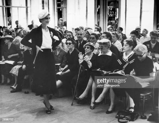 Spectators at a Dior fashion show in Paris France Centre front Marie Louise Bousquet Paris Editor of Harper's Bazaar and Carmel Snow Editor in Chief...