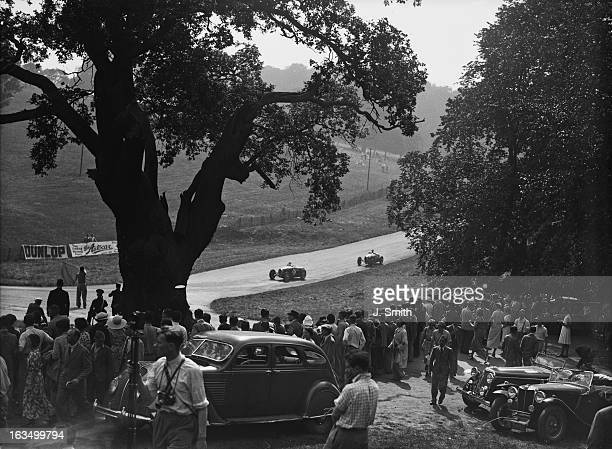 Spectators at the Junior Car Club 200 Miles Race at Donington Park circuit Leicestershire 29th August 1936 The competitor nearest the camera is a...