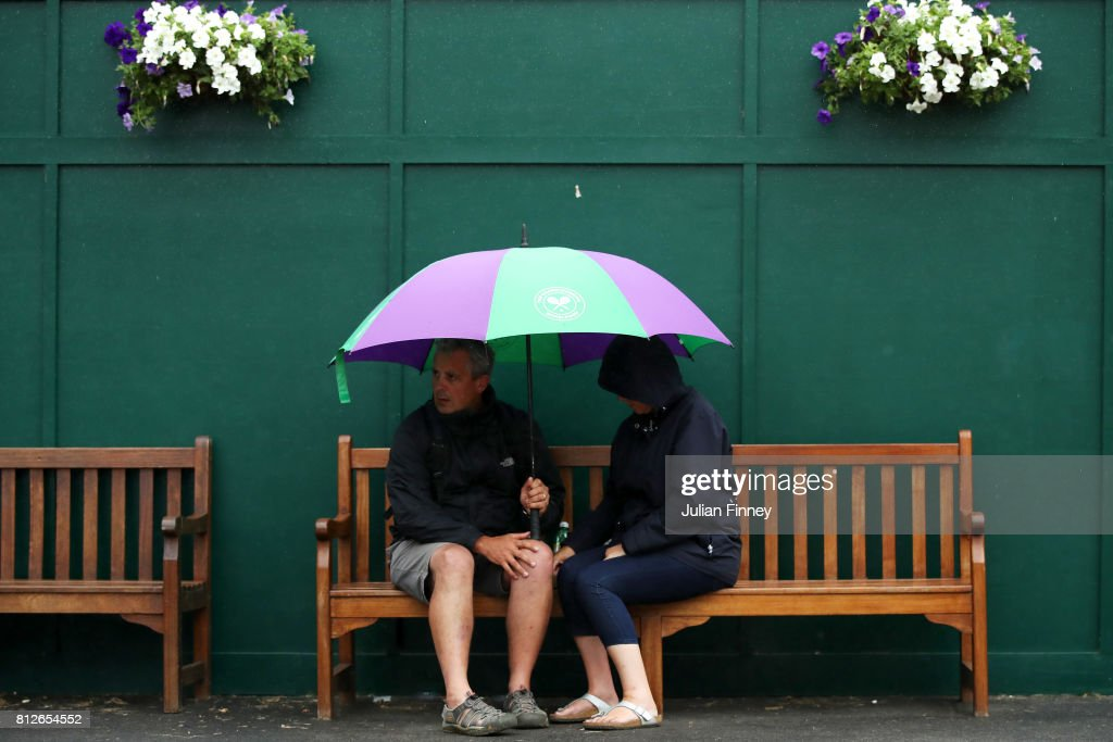 Spectators attempt to keep dry on day eight of the Wimbledon Lawn Tennis Championships at the All England Lawn Tennis and Croquet Club on July 11, 2017 in London, England.