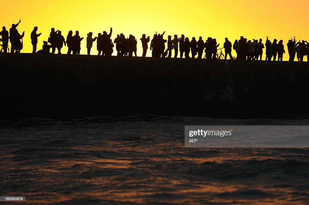 Spectators attend the arrival of British skipper Alex Thomson on his monohull 'Hugo Boss' who placed third in the 7th edition of the Vendee Globe solo round-the-world race on January 30, 2013 in Les Sables d'Olonne, western France. AFP PHOTO JEAN-SEBASTIEN EVRARD