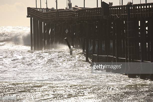 Spectators came to watch crashing waves and take photos of the dangling pilings at the damaged Ventura Pier which was closed Friday morning as high...