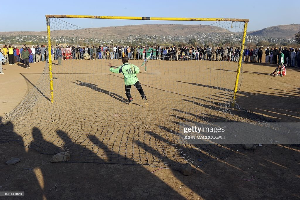 Spectators cast shadows as they watch the penalty shootout between local teams Brazil and Green Buffalos at a makeshift football field outside the Atteridgeville township near Pretoria June 16, 2010. The 2010 World Cup hosted by South Africa continues through July 11.