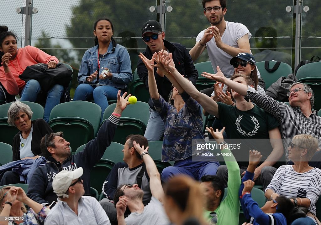 Spectators catch a ball while watching US player Julia Boserup against Switzerland's Belinda Bencic during their women's singles second round match on the fourth day of the 2016 Wimbledon Championships at The All England Lawn Tennis Club in Wimbledon, southwest London, on June 30, 2016. / AFP / ADRIAN