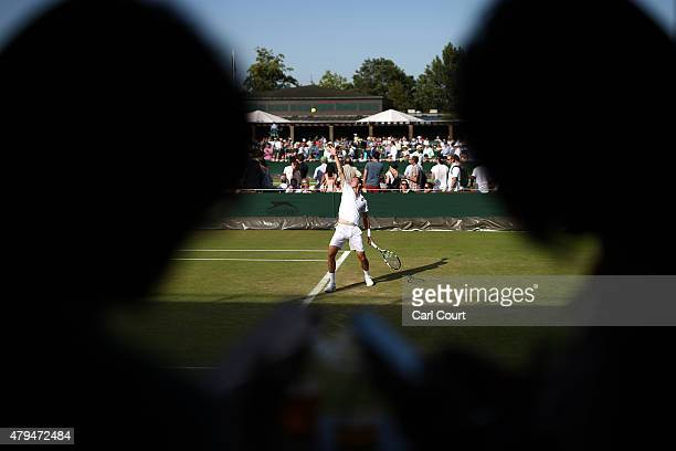 Spectators check their phones as a player serves during a match on day 6 of the Wimbledon Lawn Tennis Championships at the All England Lawn Tennis...