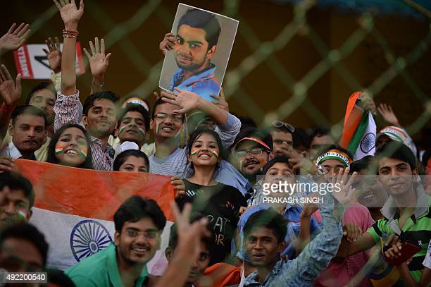 Spectators cheer ahead of the start of the first one day international cricket match between India and South Africa at Green Park Stadium in Kanpur...