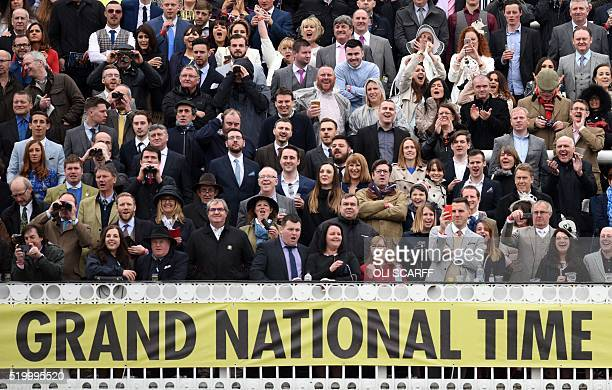 Spectators cheer as The Grand National Steeple Chase starts on the final day of the Grand National Festival horse race meeting at Aintree Racecourse...