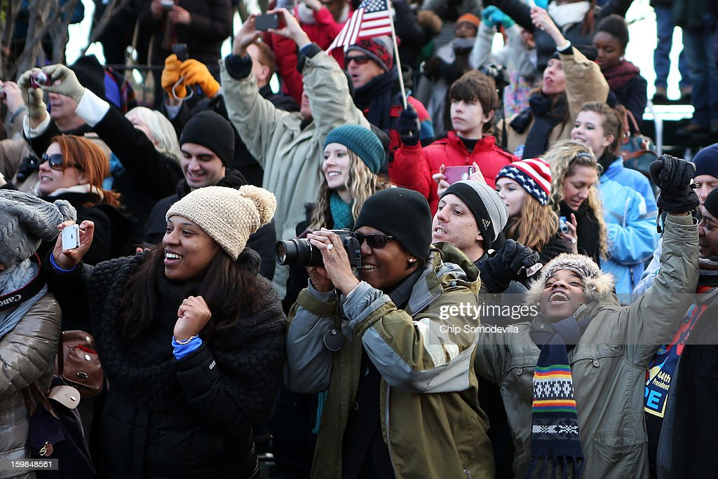 Spectators cheer as the presidential inaugural parade winds through the nation's capital January 21, 2013 in Washington, DC. Barack Obama was re-elected for a second term as President of the United States.