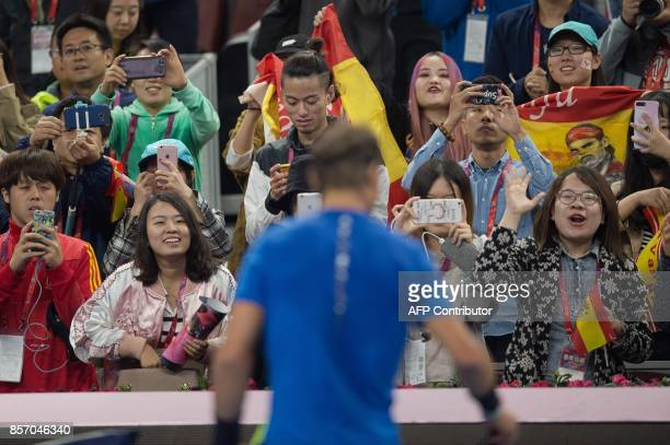 Spectators cheer for Rafael Nadal of Spain following his win in the men's singles match against Lucas Pouille of France at the China Open tennis...