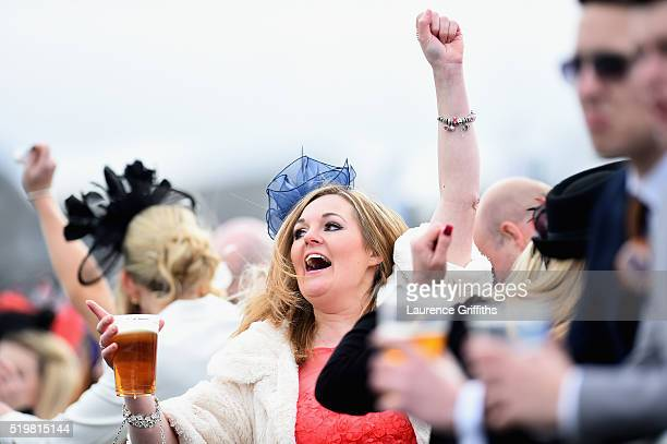 Spectators cheer on their Horses during Ladies Day at Aintree Racecourse on April 8 2016 in Liverpool England
