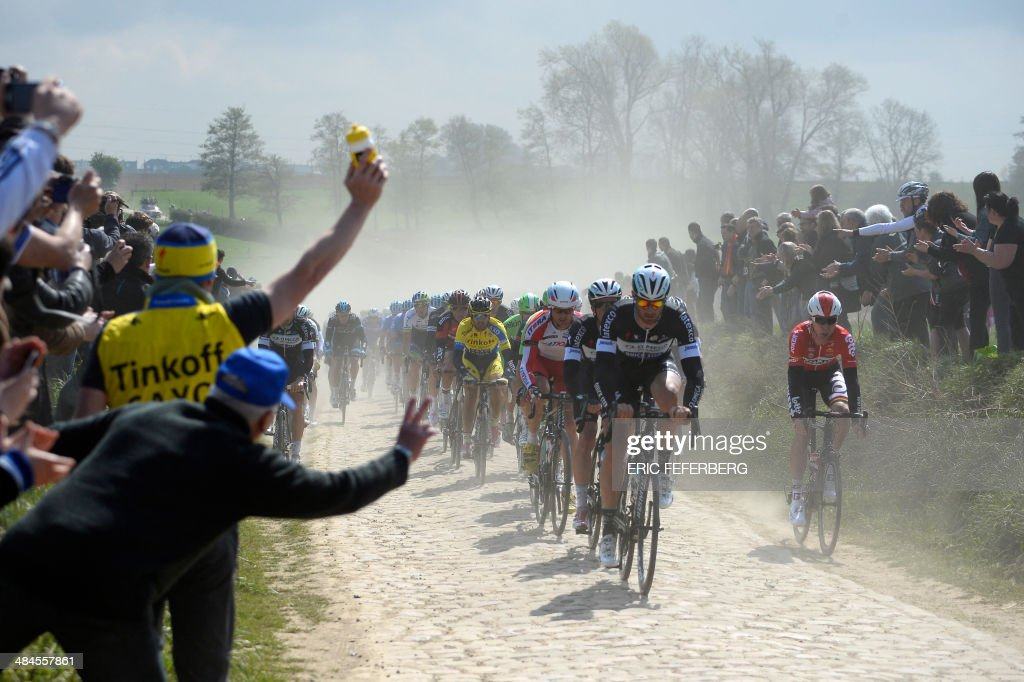 Spectators cheer riders pedaling through a cobblestoned section during the 112th edition of the Paris-Roubaix one-day classic cycling race on April 13, 2014 between Compiegne and Roubaix, northern France.
