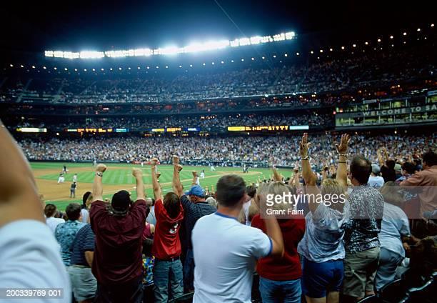 Spectators cheering at night baseball game, rear view