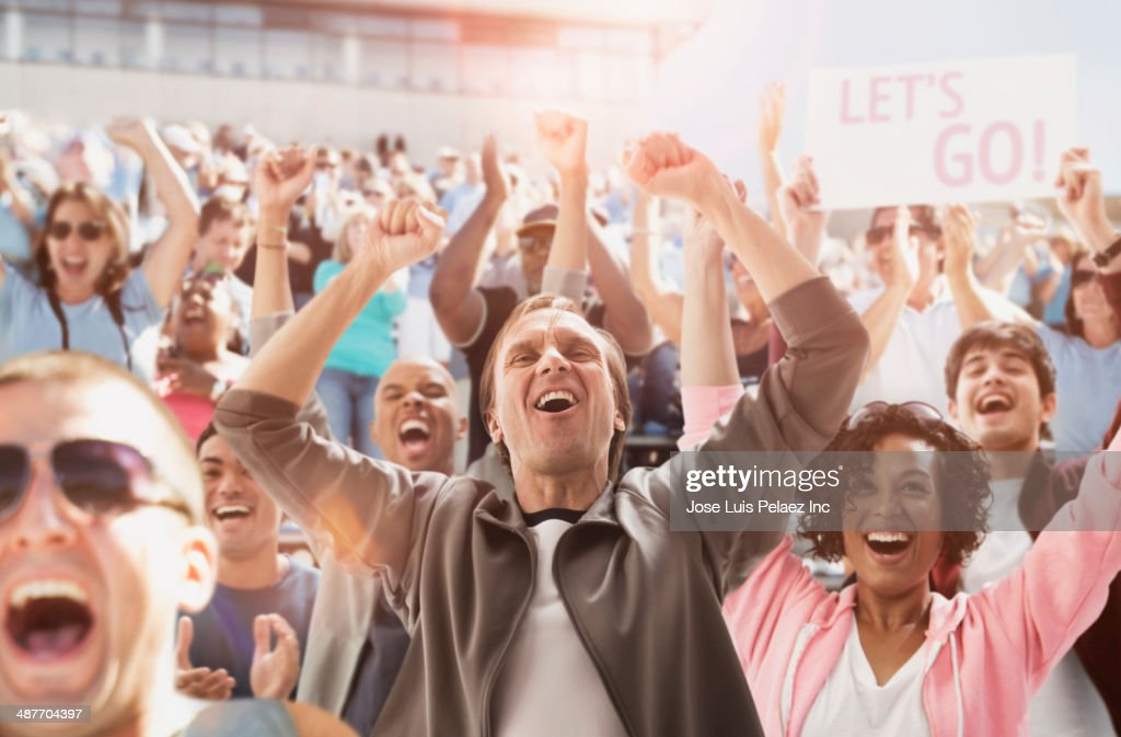 Spectators cheering at sporting event : Stockfoto