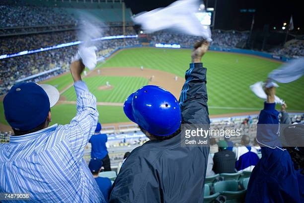 Spectators cheering  during baseball game , rear view