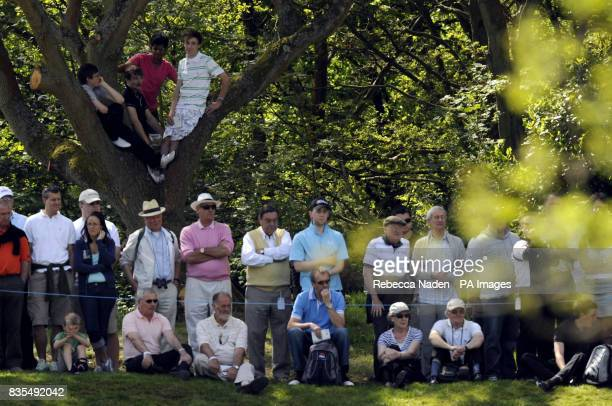 Spectators climb a tree beside the 2nd green during Round 3 of the BMW PGA Championship at Wentworth Golf Club Surrey