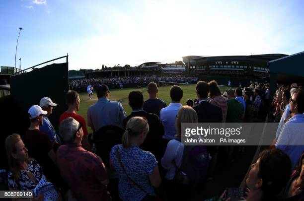 Spectators court side watch the match between Marcel Granollers and Dudi Sela on day two of the Wimbledon Championships at The All England Lawn...
