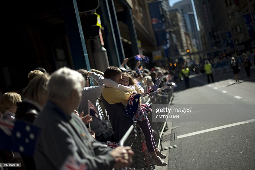 Spectators display a flag as they watch the Anzac Day march in Sydney on April 25, 2013. Tens of thousands of Australians and New Zealanders turned out on April 25 to honour their war dead, with moving tributes to fallen mates and calls not to forget those injured in conflict. AFP PHOTO / Saeed Khan
