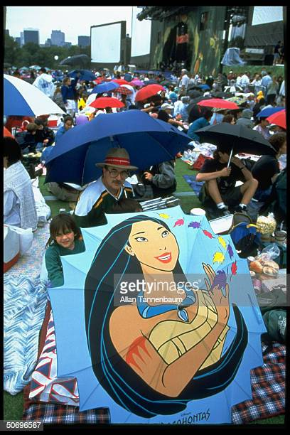 Spectators displaying umbrella opened to picture of Disney character Pocahantas at outdoor screening of film Pocahantas in Central Park