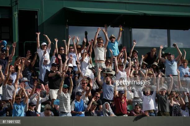 Spectators do a Mexican wave in the crowd as Czech Republic's Tomas Berdych plays against Austria's Dominic Thiem during their men's singles fourth...