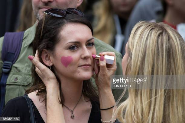 Spectators draw hearts on each others' cheeks before the start of the Great Manchester Run in Manchester north west England on May 28 2017 Britain...