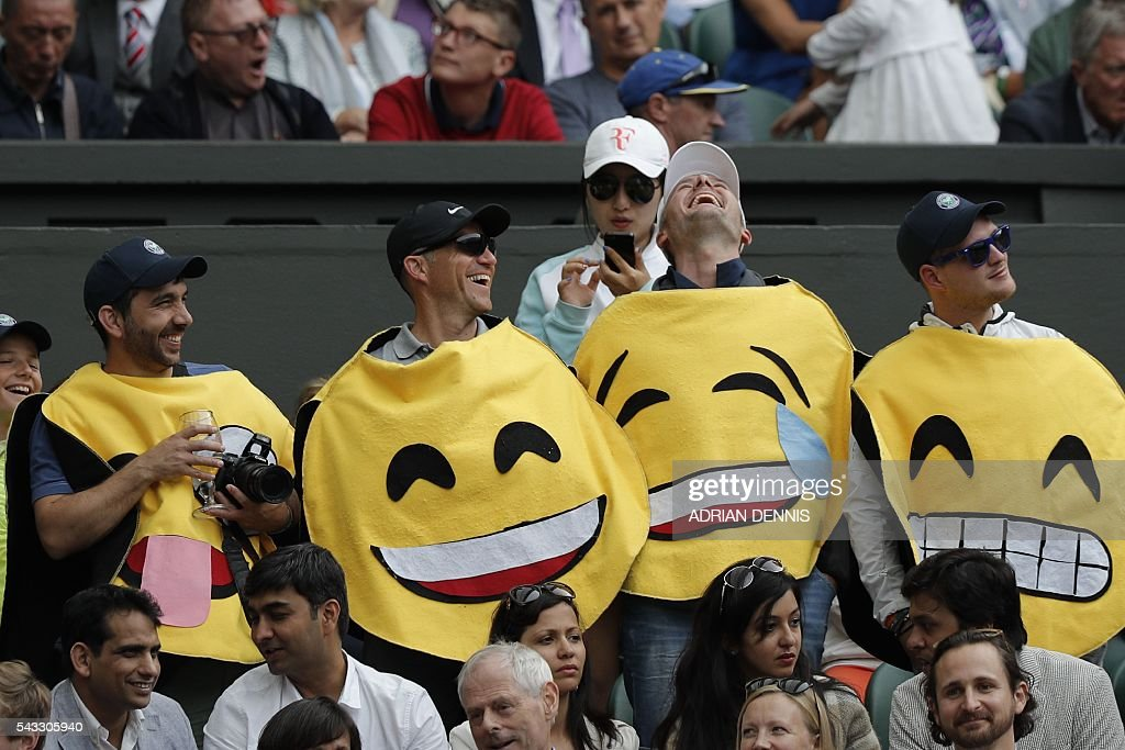 Spectators dressed as emoticons stand in the crowd watching Switzerland's Roger Federer play against Argentina's Guido Pella during their men's singles first round match on the first day of the 2016 Wimbledon Championships at The All England Lawn Tennis Club in Wimbledon, southwest London, on June 27, 2016. / AFP / ADRIAN
