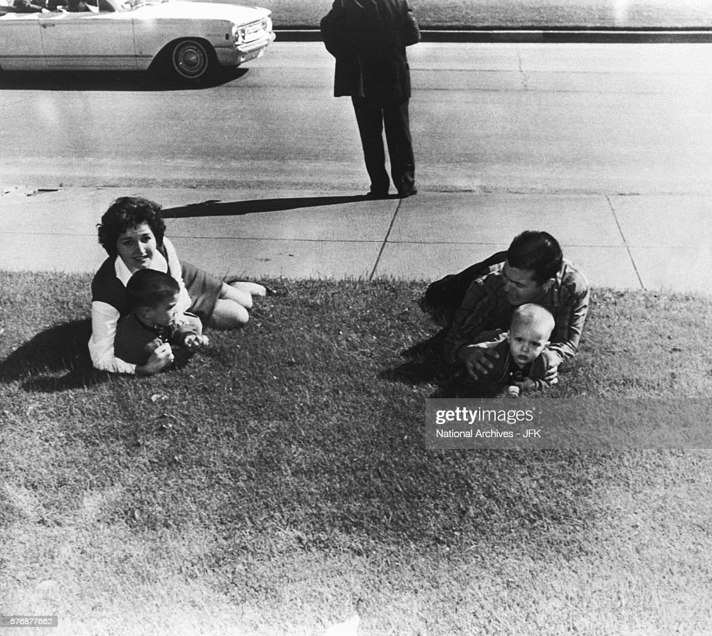 Spectators drop to the ground after shots are fired at Dealy Plaza during the assassination of President Kennedy on November 22, 1963.